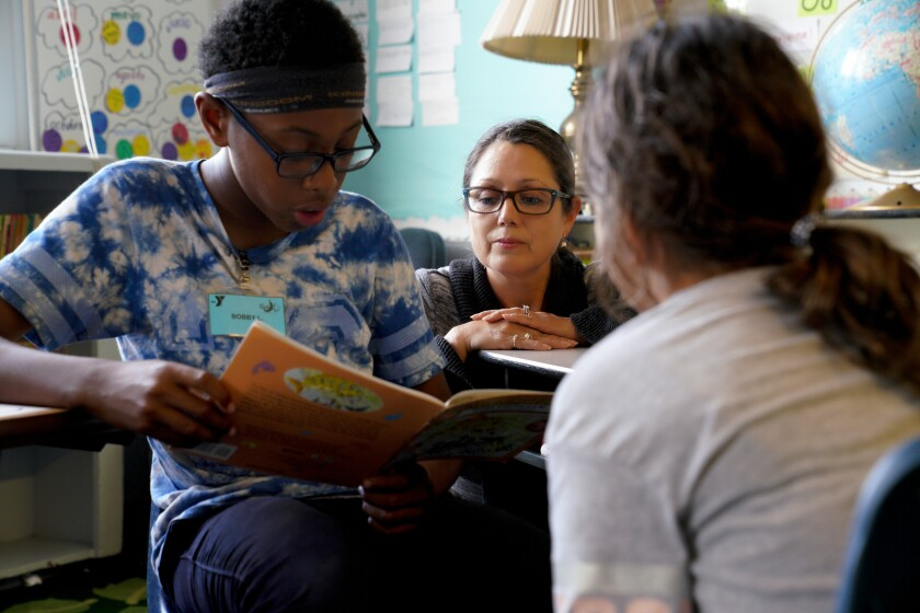Assistant Principal Margarita Morales (center) works with Bobby Latson and Isabella Rincon during an after school progam at Empower Charter Elementary School in Linda Vista on Wednesday, Oct. 9, 2019.