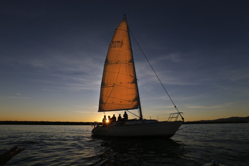 The sunset illuminates the sail as a crew of sailors glides across the water in Marina del Rey. Residents are at odds with Los Angeles County officials over a planned hotel development.