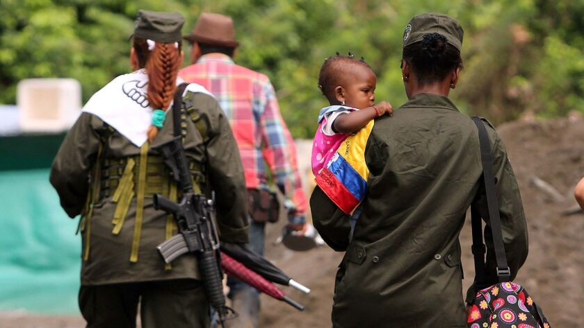 Guerrilla women from the Revolutionary Armed Forces of Colombia carry their babies in a camp site in Tumaco, Colombia.