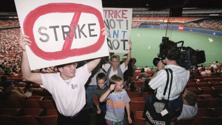 Robert Martinez, left, leads a group of protesters out of the stands after the third inning of the game between the San Diego Padres and the Houston Astros in Houston, on Thursday, August 11, 1994. Players were set to strike after the completion of that day's games.