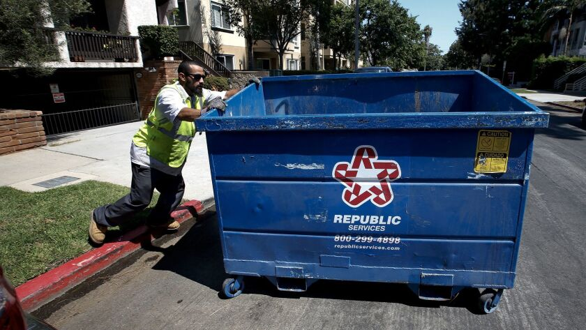 An employee with Athens Services, the trash hauler chosen by the city to serve the Westisde, moves a