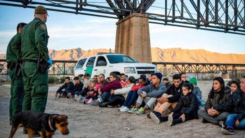 A group of about 30 Brazilian migrants who just crossed the border sit on the ground near U.S. Border Patrol agents on the U.S.-Mexico border in Sunland Park, N.M.