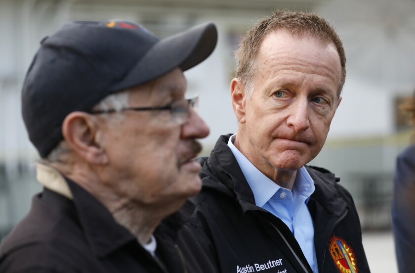 LAUSD Supt. Austin Beutner listens as School Board member George McKenna speaks at a meal distribution location at Dorsey High School on March 18.