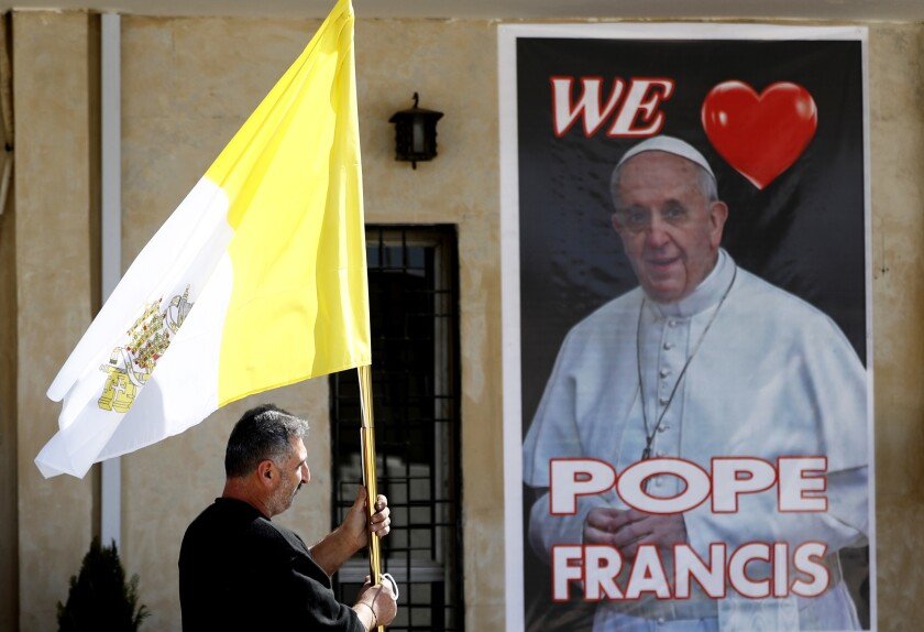 A Christian priest holds a Vatican flag as he walks by a poster of Pope Francis during preparations for the Pope's visit in Mar Youssif Church in Baghdad, Iraq, Friday, Feb. 26, 2021. (AP/Photo/Hadi Mizban)