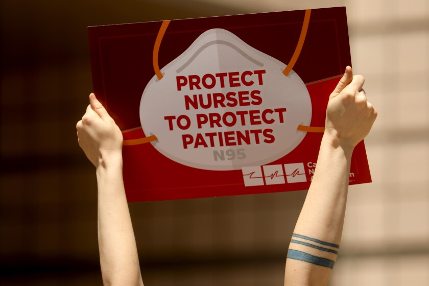 """Two arms hold up a sign saying """"protect nurses to protect patients"""""""