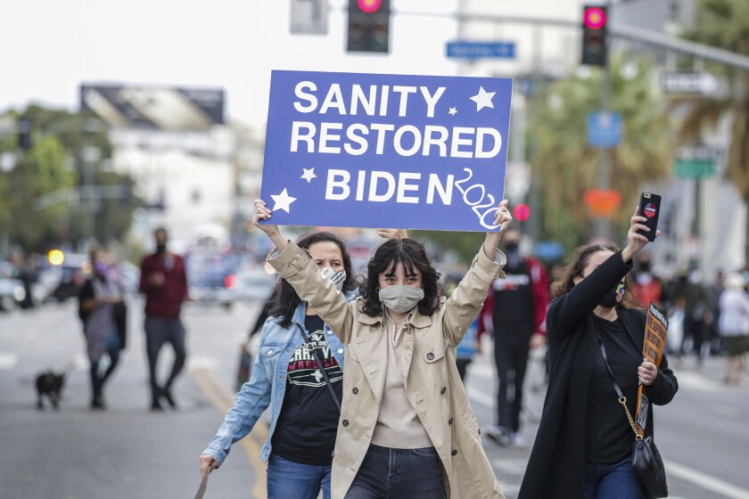 A woman holds up a sign that reads Sanity restored, Biden 2020