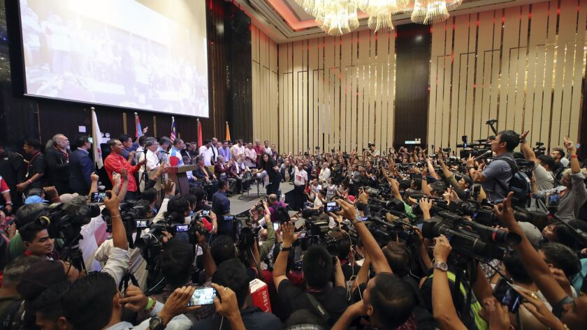 Opposition leader and 92-year-old former autocrat Mahathir Mohamad, center on stage, celebrates victory Wednesday at a hotel in Kuala Lumpur, Malaysia.