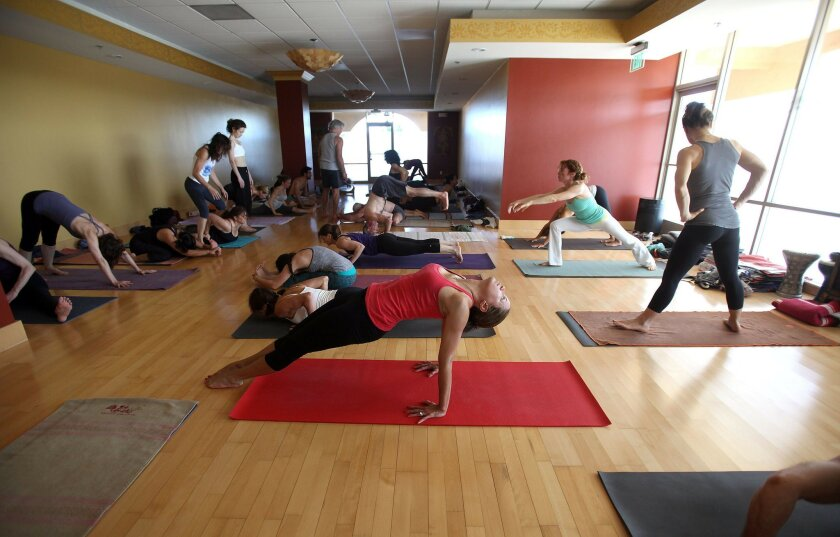 People gathered at Ashtanga Yoga in Carlsbad on Thursday for a class taught by Tim Miller, a board member with the Jois Foundation. John Gastaldo/U-T San Diego