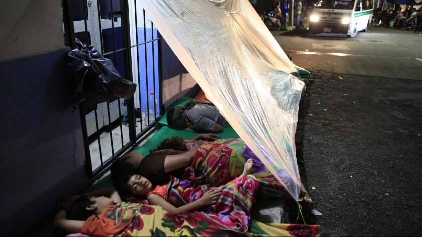Migrants unable to find shelter sleep in the street outside the offices of the Mexican Commission fo