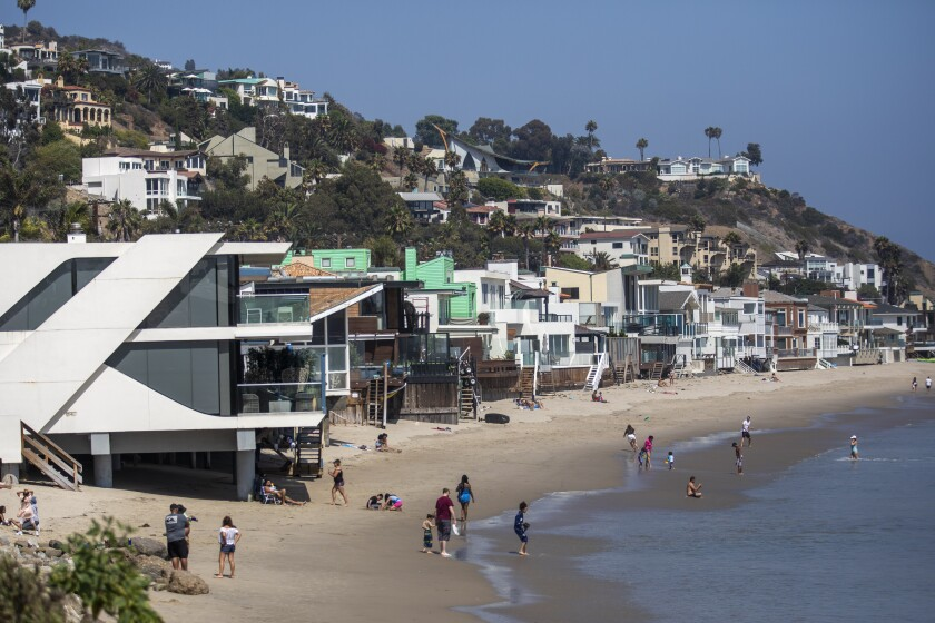 A thin strip of beach with houses on the sand