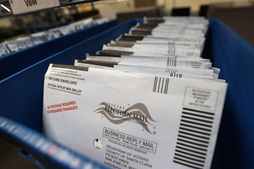 Mail-in ballots sit in trays before being sorted at the Santa Clara County registrar of voters office.