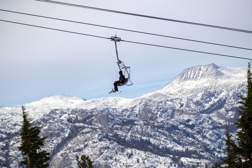 A snowboarder rides a chair lift at Mammoth Mountain in November 2020.