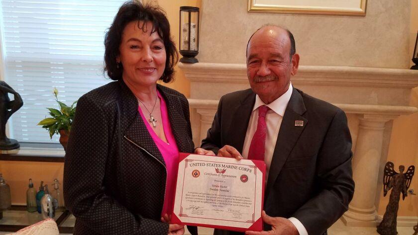 Ursula Kuster receiving her award from USO Advisory Board member Tom Garcia.