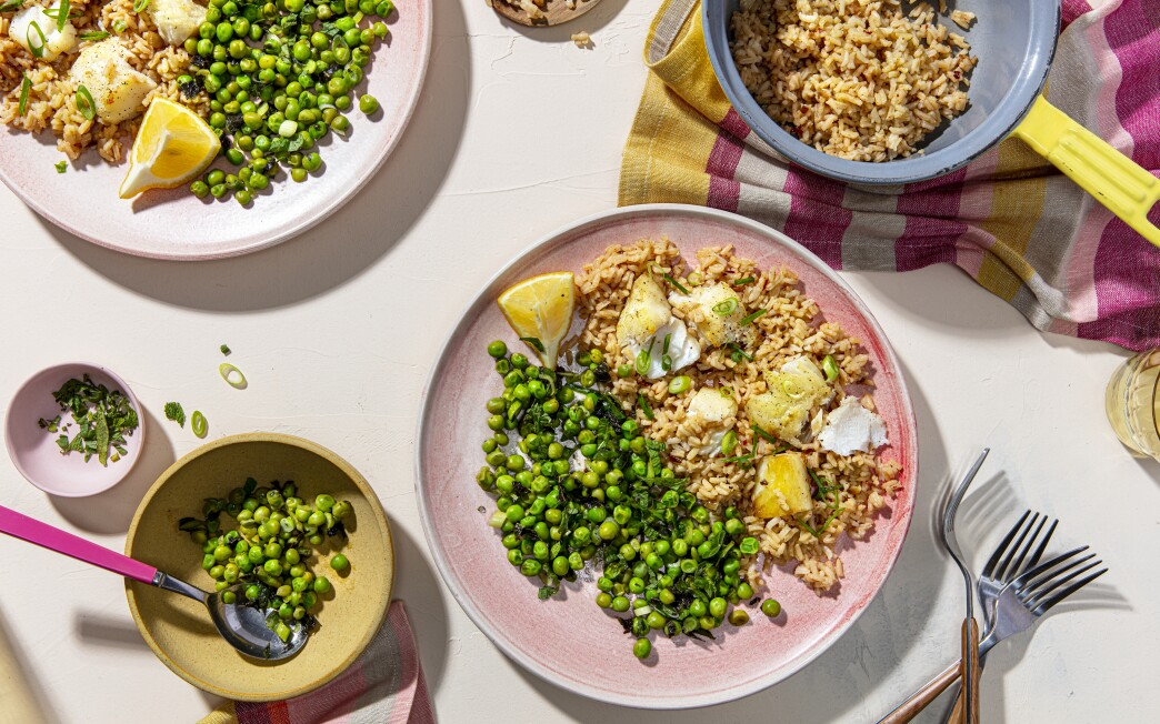 Toasted spices perfume rice and roasted fish in this simple dinner served with peas dressed with lemon and mint.