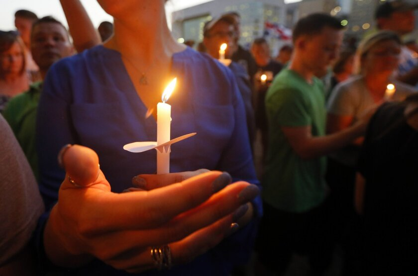 A woman holds a crucifix and a lit candle as she and hundreds of others take part in a candlelight vigil at City Hall, Monday, July 11, 2016, in Dallas. Four Dallas police officers and one DART officer were killed in Thursday's attack. (AP Photo/Tony Gutierrez)