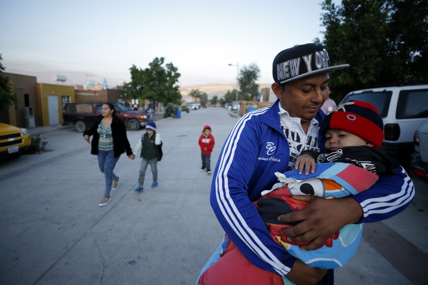 A man carries his youngest son as the family leaves their home in Tijuana for an asylum hearing in San Diego.