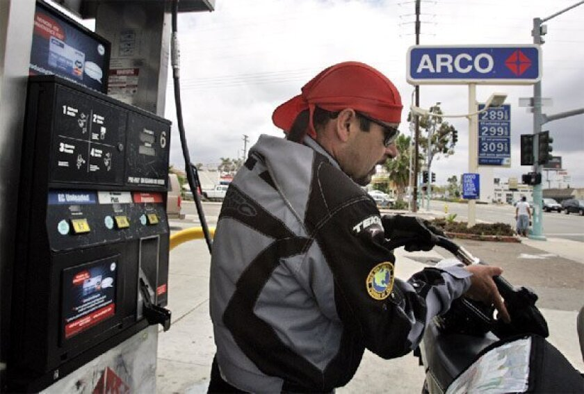 Alejandro Alcalde of Ensenada filled up his motorcycle yesterday at a gas station in City Heights. 