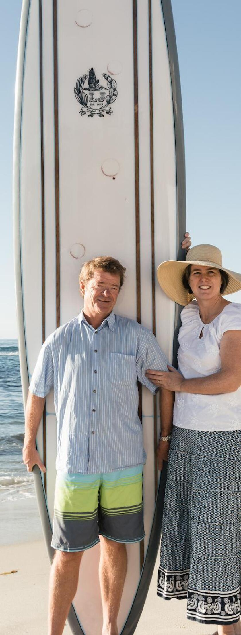Lowell and Anne Jooste pose with a surfboard crafted by local artist, Tim Bessell. The wine rings were placed by each member of the Jooste family and intentionally designed into it.