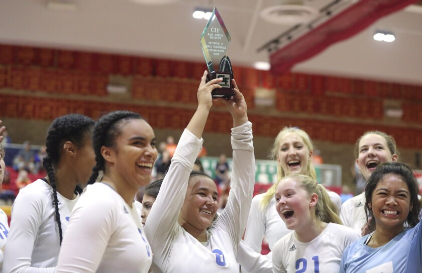 Maranatha Christian's Alysha Buffini holds up the trophy after the Eagles clinched the San Diego Section Division II championship with a win over Valhalla on Saturday at Cathedral Catholic High.