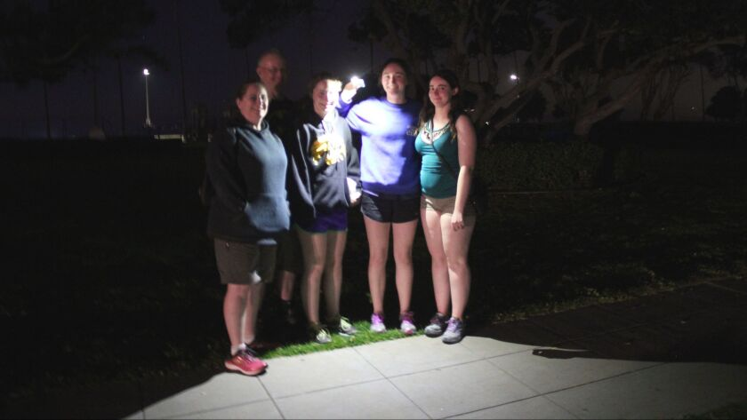 The David family, visiting from Arizona, use a cellphone flashlight to find their way around La Jolla Shores, the night of March 15.