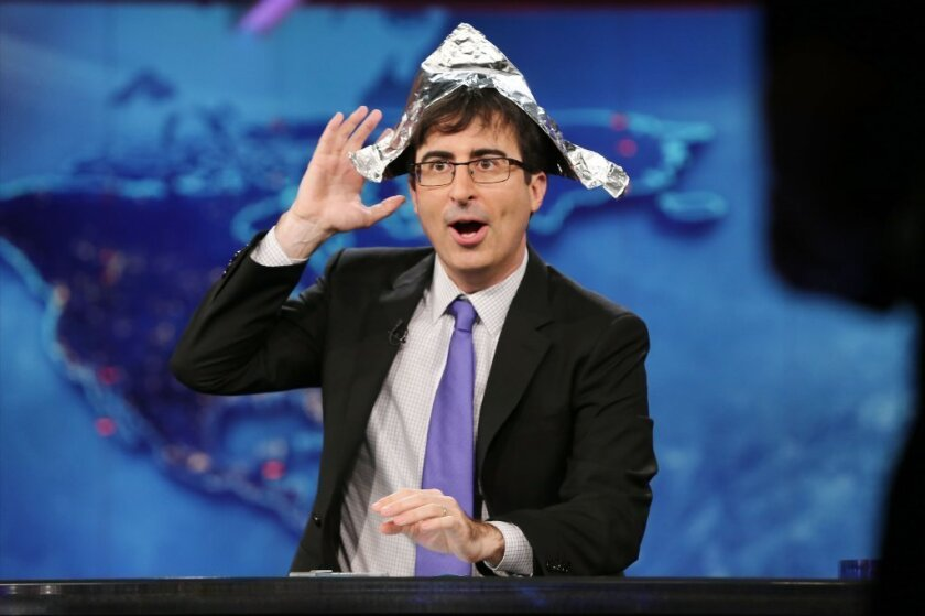 """John Oliver puts on a tin foil hat to foil government surveillance on his first night as temporary host of Comedy Central's """"The Daily Show."""""""