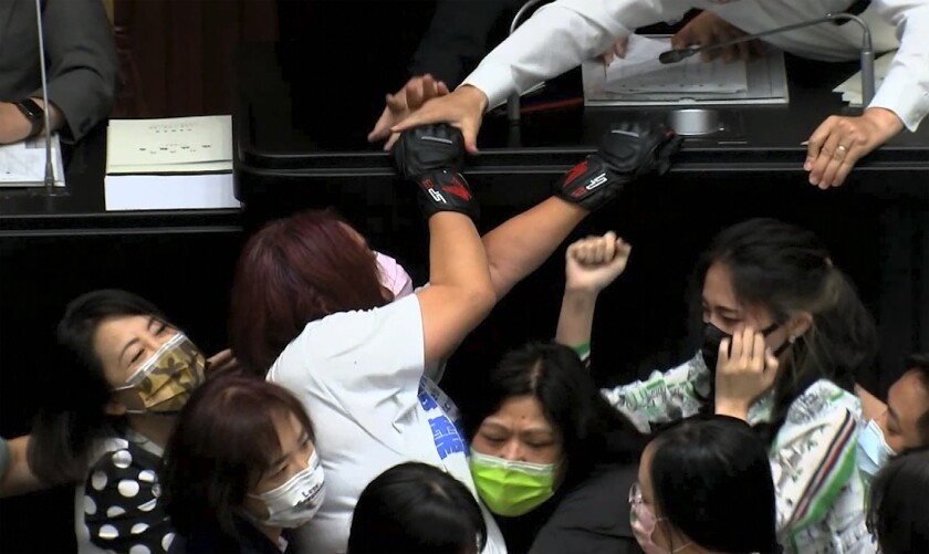 In this image taken from video by Taiwan's EBC, opposition Nationalist party lawmaker Chen Yu-jen, in white shirt, is grabbed by ruling Democratic Progressive Party lawmakers as she tries to climb onto the podium during a parliament session in Taipei, Taiwan, Tuesday, Sept. 28, 2021. Taiwan's legislature on Tuesday descended into a rowdy brawl on Tuesday, after opposition lawmakers interrupted an important policy address and rushed the podium. (EBC via AP )