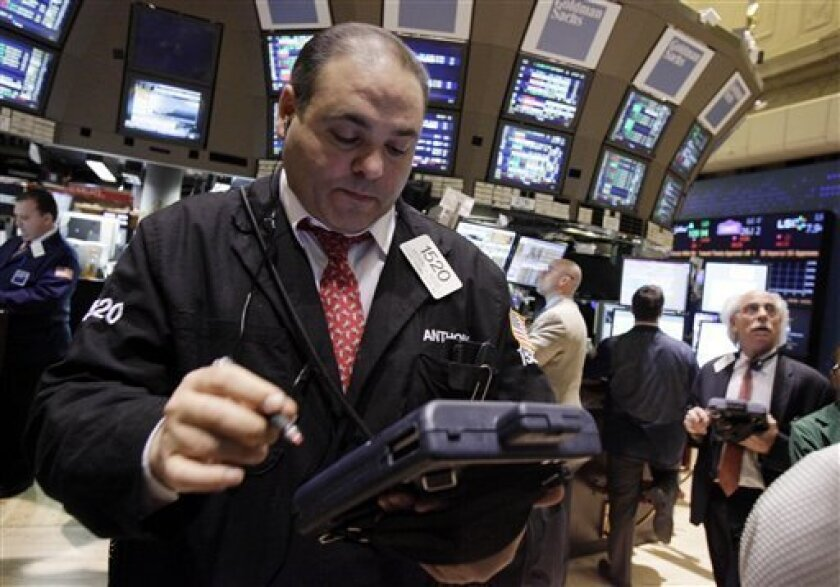 In this Feb. 3, 2012 photo, trader Anthony Riccio, left, works on the floor of the New York Stock Exchange. Stocks were trading lower on Tuesday, Feb. 7,2012, as talks dragged on in Greece to agree the terms of a second bailout _ and avoid looming bankruptcy _ despite intense pressure from the country's euro partners. (AP Photo/Richard Drew)
