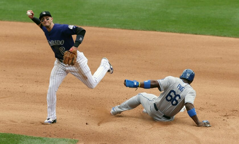 Colorado Rockies shortstop Troy Tulowitzki, left, throws to first base after forcing out Los Angeles Dodgers' Yasiel Puig at second base on the front end of a double play hit into by Adrian Gonzalez to end the top of the fourth inning of a baseball game in Denver on Saturday, June 7, 2014. (AP Photo/David Zalubowski)