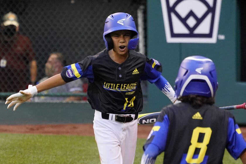 Torrance, Calif.'s Skylar Vinson (14) celebrates as he returns to the dugout after scoring on a single.