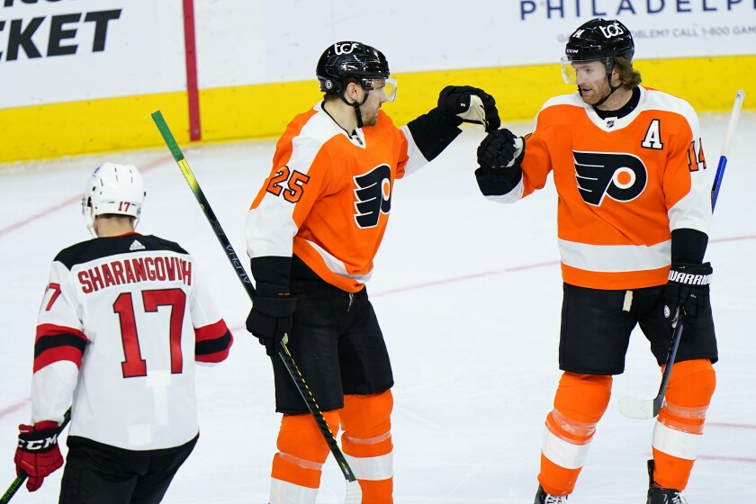 Philadelphia Flyers' James van Riemsdyk (25) and Sean Couturier (14) celebrate past New Jersey Devils' Yegor Sharangovich (17) after a goal by van Riemsdyk during the third period of an NHL hockey game, Monday, May 10, 2021, in Philadelphia. (AP Photo/Matt Slocum)
