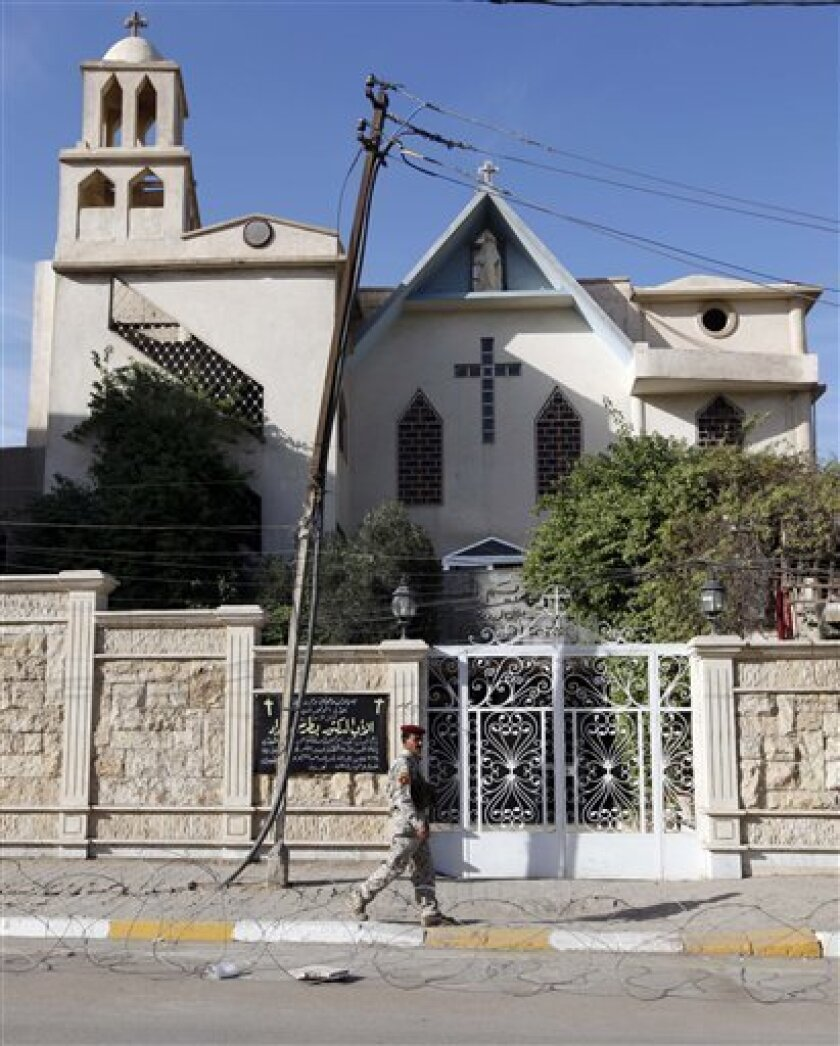 An Iraqi police officer stands guard outside a closed church in Baghdad, Iraq, Wednesday, Dec. 22, 2010. Church officials in Iraq say they have canceled some Christmas festivities in two northern cities over fears of insurgent attacks. (AP Photo/Hadi Mizban)