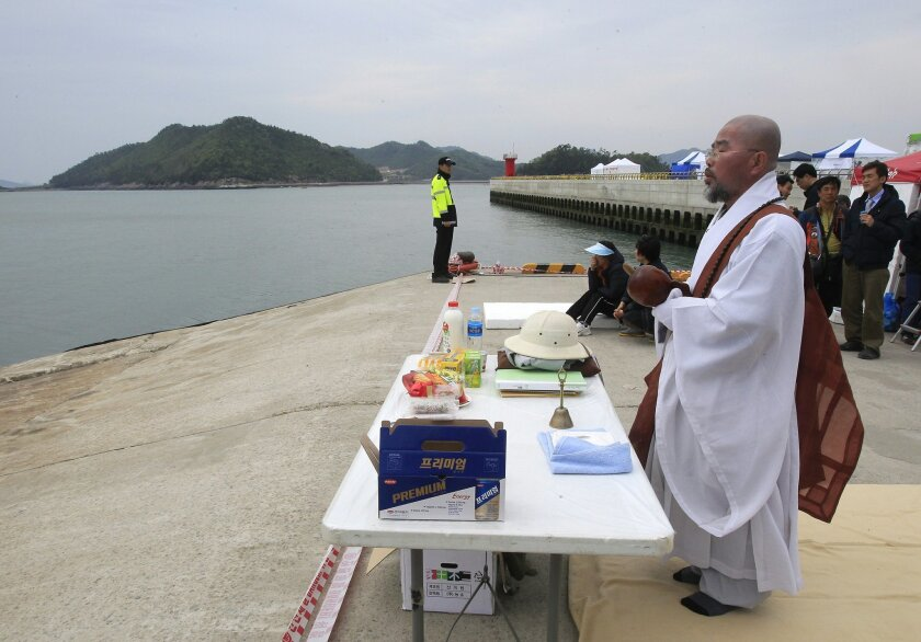 In this April 26, 2014 photo, Buddhist monk, Bul Il offers prayers to wish for the safe return of passengers of the sunken ferry Sewol in Jindo, South Korea. Bul Il came from the southeastern port city of Busan to help the families of the more than 100 still missing in the sunken South Korean ferry. (AP Photo/Ahn Young-joon)
