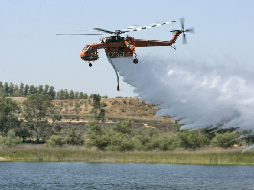 The helitanker demonstrated its abilities at Lower Otay Reservoir yesterday.  It can carry seven times as much water as the city's two current helicopters  and fly for 2 1/2 hours without refueling. (Earnie Grafton / Union-Tribune)