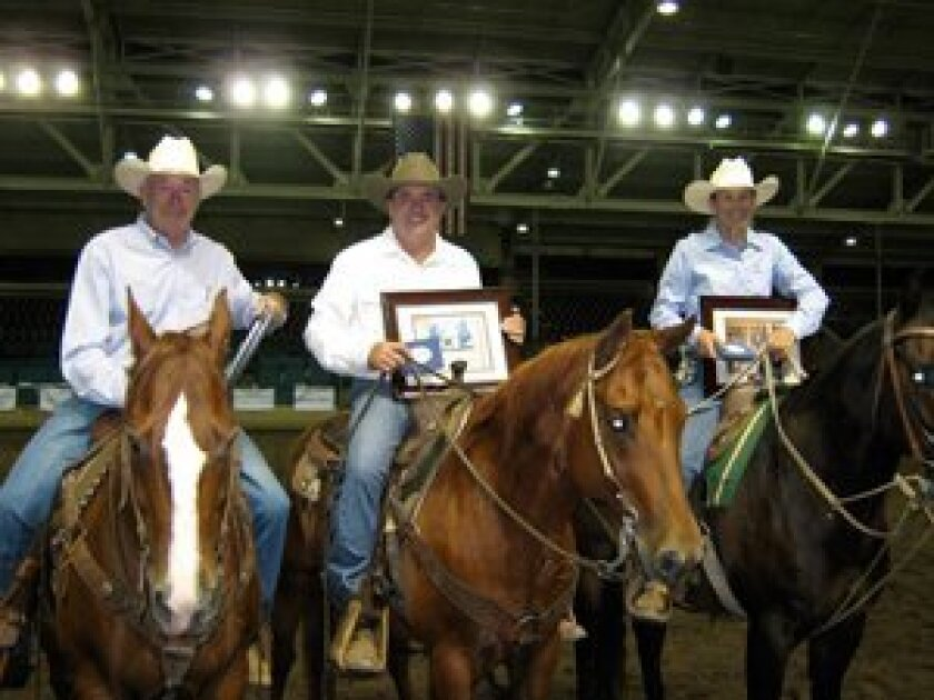 """The 2011 """"Teens, Jeans and Dreams"""" team penning winners are Bill Cuddeback, George Scott, who won on Catherine Nicholas' horse, Boonie, and Sherry Songer.  They are displaying photos that were created by the foster students at San Pasqual Academy.  This year's event will be held on Saturday, Sept."""