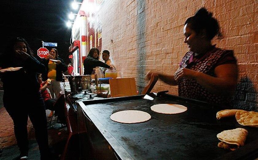 A woman heats tortillas at a sidewalk food stall along Cesar Chavez Avenue in Boyle Heights. Food vendors who gather illegally in the area recently showed up at Los Angeles City Hall to complain that they have become the target of a police effort to clean up the neighborhood.