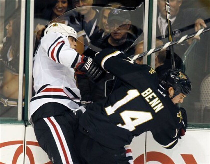 Chicago Blackhawks defenseman Niklas Hjalmarsson (4), of Sweden, and Dallas Stars left wing Jamie Benn break the glass as they slam into the boards in the third period of an NHL hockey game, Friday, Oct. 7, 2011, in Dallas. (AP Photo/Sharon Ellman)