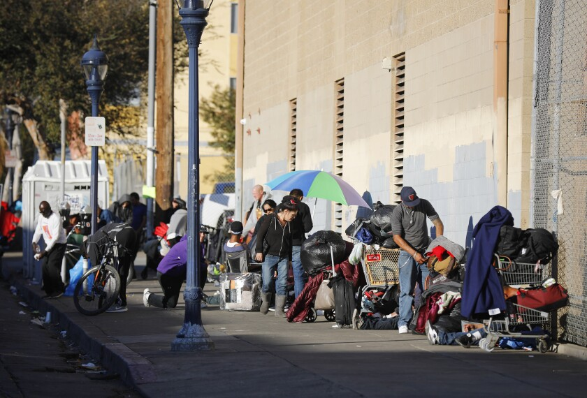 Homeless people line the sidewalk on 16th Street in San Diego on Dec. 16, 2019.
