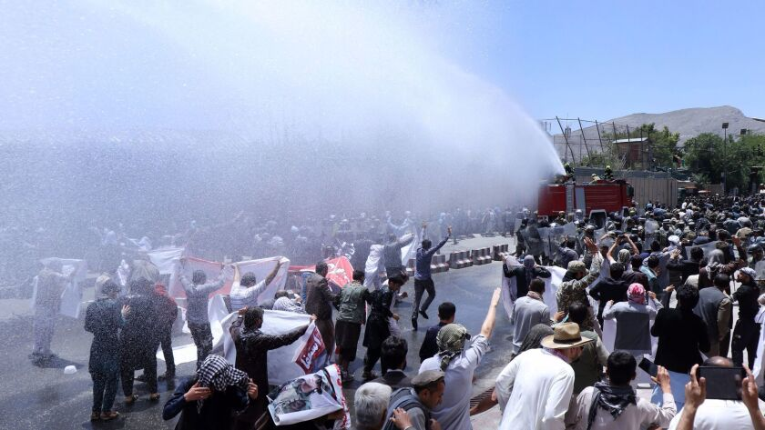 Afghan security officials use a water cannon June 2 to disperse demonstrators in Kabul, the capit.