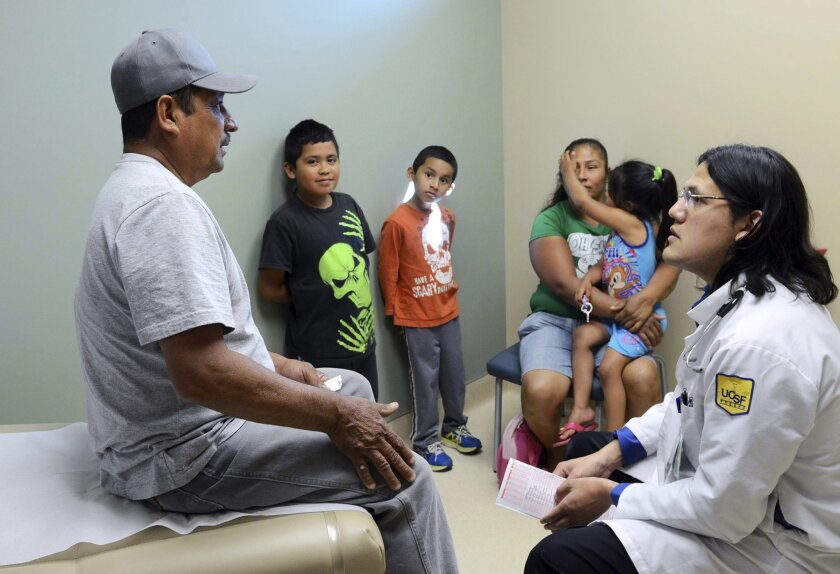 A farm laborer and his family speak to a doctor at a clinic in Fresno in 2014.