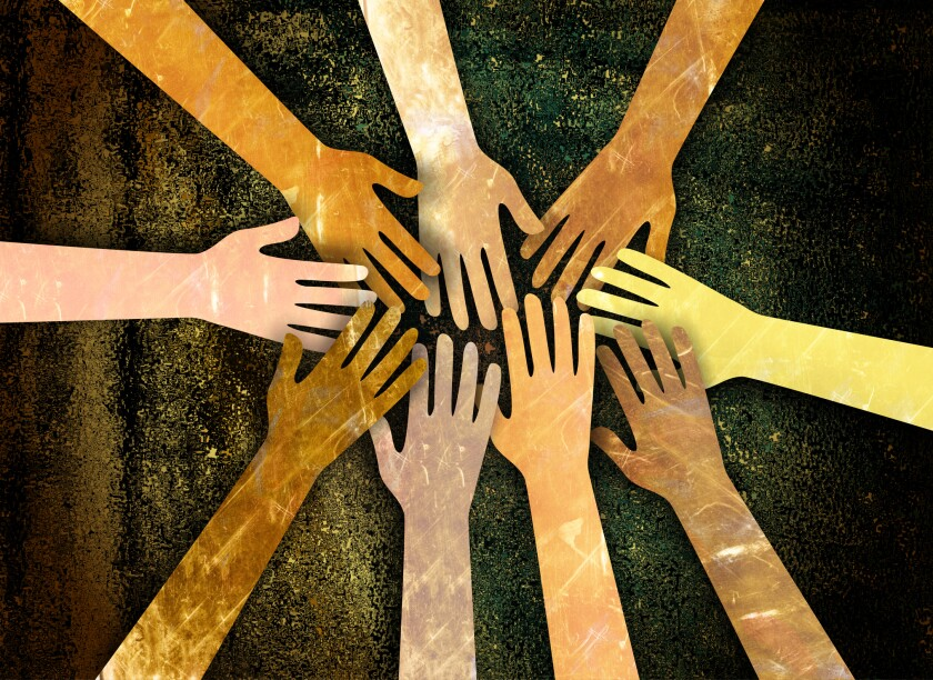 A group of diverse hands reaching together in unity and support.