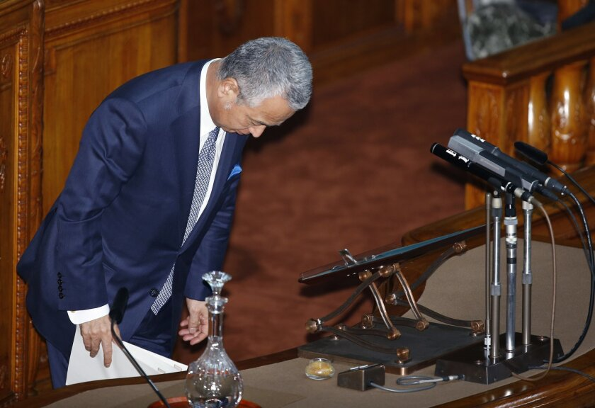 Japanese Economy Minister Akira Amari brows before answering questions at the upper house of the parliament in Tokyo, Thursday, Jan. 28, 2016. Later, Amari said he intends to resign due to allegations he accepted bribes from a construction company in a nationally televised news conference. (AP Photo/Shizuo Kambayashi)