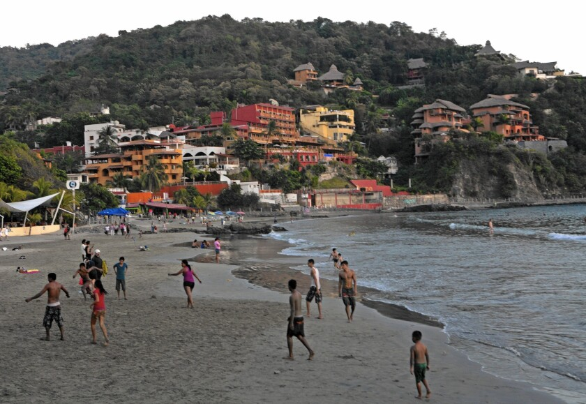 Beachgoers enjoy a Sunday evening at Playa la Madera in Zihuatanejo, Mexico, where humble restaurants and hotels -- not to mention the water -- beckon.