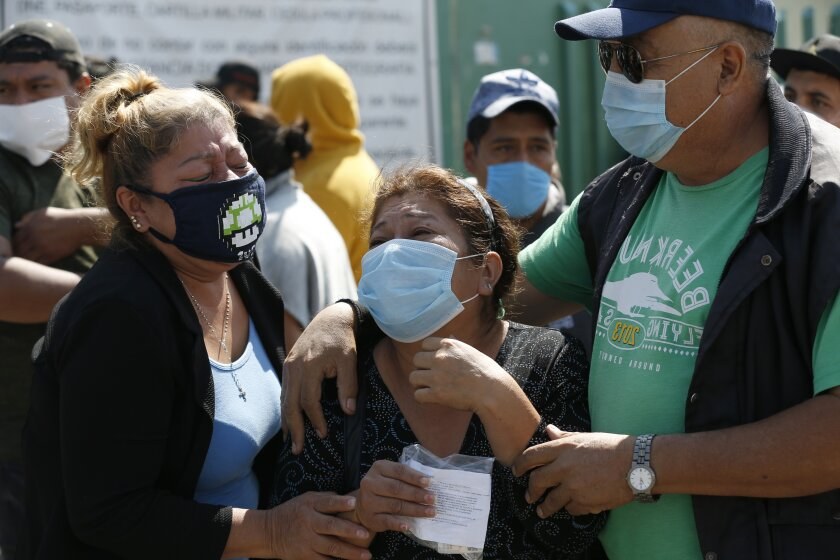 Isabel Cordero, center, and her relatives grieve outside the General Hospital in Ecatepec, Mexico City, after learning that her husband, Jose Luis Rojas, died of respiratory distress on May 2, 2020.