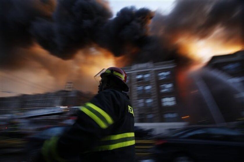 Firefighters battle a blaze in an apartment building in Philadelphia, Monday, Jan. 10, 2011. Firefighters said the building had been evacuated safely and there were no reports of injuries. (AP Photo/Matt Rourke)
