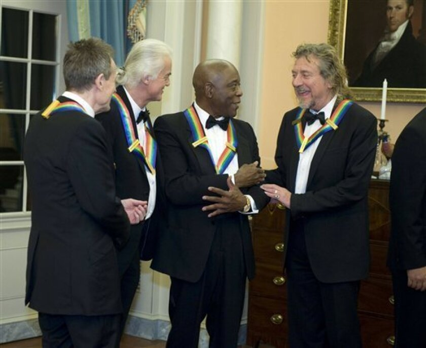 2012 Kennedy Center Honorees and members of Led Zeppelin John Paul Jones, left, Jimmy Page, second from left, and Robert Plant, right, talk with fellow 2012 Kennedy Center Honoree Buddy Guy at the end of the State Department Dinner for the Kennedy Center Honors gala Saturday, Dec. 1, 2012 at the State Department in Washington. (AP Photo/Kevin Wolf)