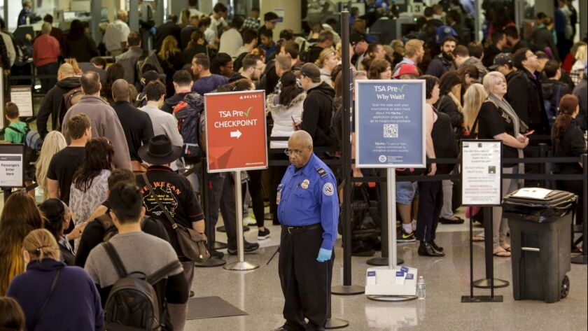 A TSA agent keeps an eye on travelers going through security at LAX.