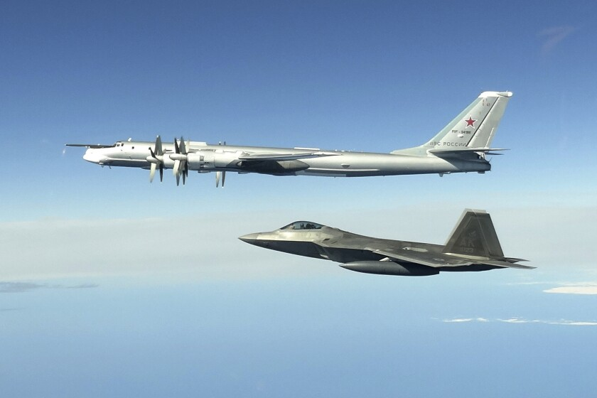Russian Tu-95 bomber and U.S. F-22 Raptor fighter