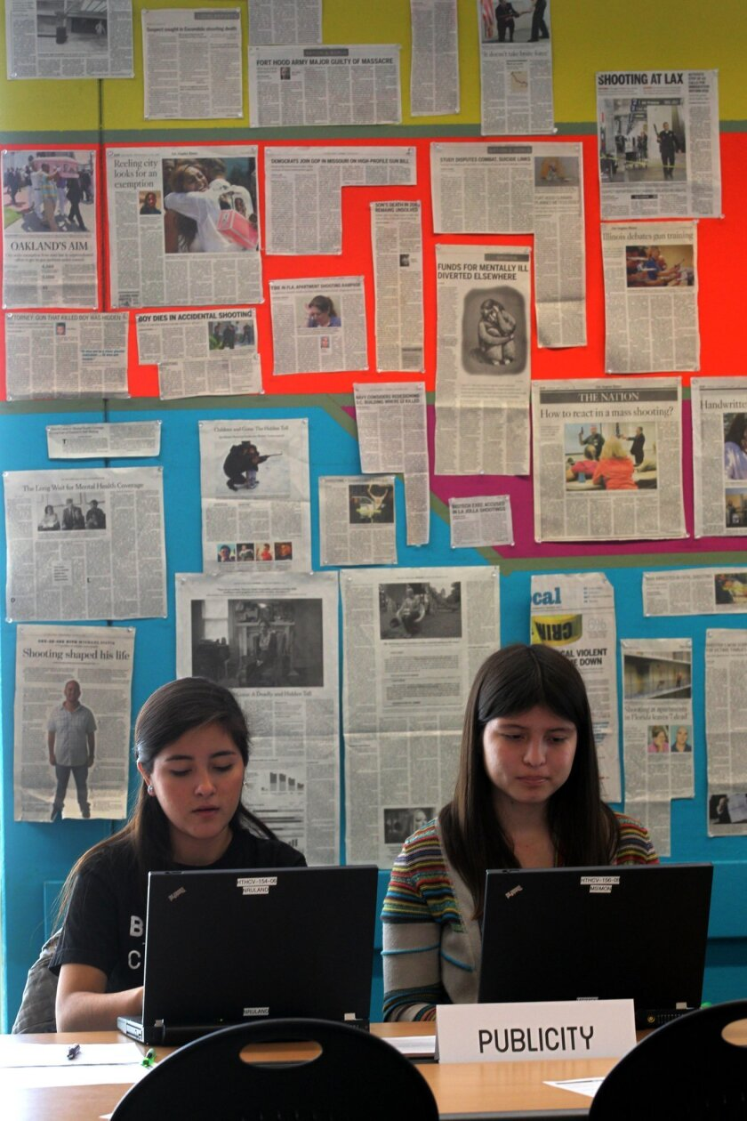 Isabella Botello and Karen Quezada, on the right, both juniors at High Tech High, worked on the classes' Beyond The Crossfire project against a backdrop of news clippings from recent shootings around the country.