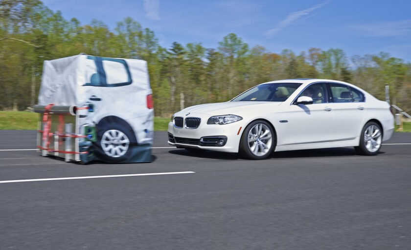 The BMW 5 series brakes for the target in an Insurance Institute for Highway Safety test. The car earns a superior rating when equipped with an optional camera and radar system.