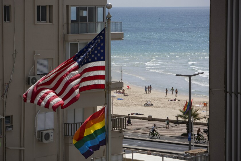 FILE - In this Thursday, June 12, 2014 file photo, a U.S. flag is raised alongside a pride flag on the U.S. Embassy a day before the Gay Pride Parade in Tel Aviv, Israel. (AP Photo/Oded Balilty, File)